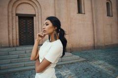 Señora en vestido contra el edificio antiguo con mirada pensativa Fotografía de archivo