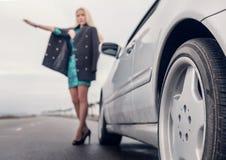 Señora en zapatos del tacón alto con el coche broked en el camino Imagen de archivo