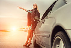 Señora en zapatos del tacón alto con el coche broked en la carretera Imagen de archivo