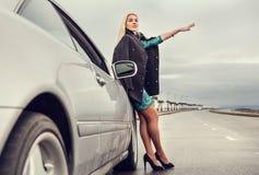 Señora en zapatos del tacón alto con el coche broked en la carretera Fotografía de archivo