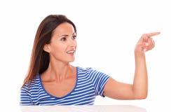 Señora encantadora en camiseta azul que señala a su izquierda Fotografía de archivo