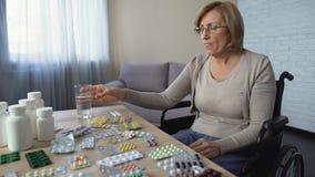 Señora enferma deprimida en la silla de ruedas que toma el tratamiento de lesión de la medicina del analgésico metrajes