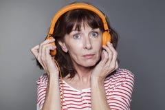 Señora envejecida centro que tira del auricular lejos del oído Imagen de archivo