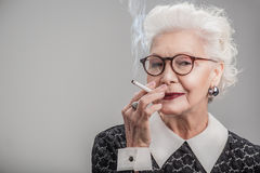 Señora envejecida feliz que goza del cigarrín Foto de archivo libre de regalías