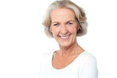 Señora envejecida sonriente feliz que hace frente a la cámara imagenes de archivo