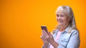 Señora envejecida sonriente que mecanografía en smartphone y que guiña, tarifas bajas para los jubilados imagenes de archivo