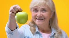 Señora envejecida sonriente que muestra la manzana verde en el fondo amarillo, atención sanitaria, detox almacen de metraje de vídeo