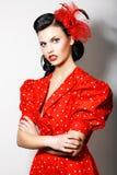 Señora estricta elegante en vestido retro rojo con las manos cruzadas. Brunette orgulloso Foto de archivo