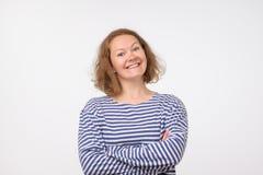 Señora europea sonriente en el pulover marino que mira la cámara, en fondo gris fotos de archivo