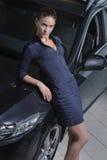 Señora expresiva de la belleza que se coloca al lado de su coche Fotos de archivo libres de regalías