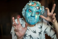 Señora fantasmagórica con la máscara que hace magia con sus fingeres Fotografía de archivo libre de regalías
