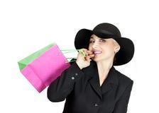 Señora feliz en un traje de negocios y un sombrero, una bolsa de papel Foto de archivo libre de regalías