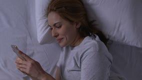 Señora feliz que charla en smartphone con querido, mintiendo en cama, relaciones blandas almacen de metraje de vídeo