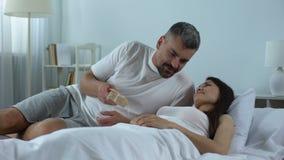 Señora feliz que despierta por mañana, marido querido que presenta a la esposa con el regalo metrajes