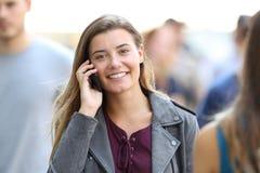 Señora feliz que invita al teléfono que le mira Imagenes de archivo