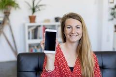 Señora feliz que muestra una pantalla elegante en blanco del teléfono que se sienta en un sofá Imagenes de archivo