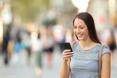 Señora feliz que usa un teléfono elegante que se coloca en la calle Imágenes de archivo libres de regalías