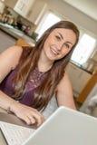 Señora femenina que trabaja en el ordenador portátil en cocina Imágenes de archivo libres de regalías