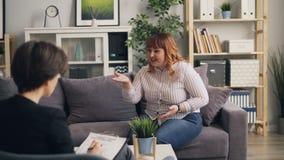 Señora gorda infeliz que abre al psicólogo en oficina moderna almacen de metraje de vídeo