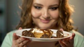 Señora gorda que mira con la admiración la placa con el apego de la comida de los dulces y de los caramelos imágenes de archivo libres de regalías