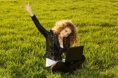 Señora hermosa con su ordenador portátil en hierba Fotos de archivo libres de regalías