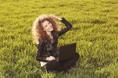Señora hermosa con su ordenador portátil en hierba Fotos de archivo
