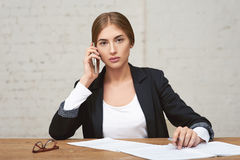 Señora hermosa del negocio que habla en el teléfono Ella comprueba informes Fotografía de archivo libre de regalías
