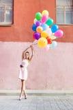 Señora hermosa en el equipo retro que lleva a cabo un manojo de betwe de los globos Imagen de archivo libre de regalías