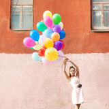 Señora hermosa en el equipo retro que lleva a cabo un manojo de betwe de los globos Fotos de archivo libres de regalías