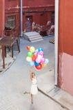 Señora hermosa en el equipo retro que sostiene un manojo de globos Imágenes de archivo libres de regalías