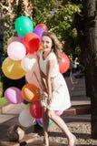 Señora hermosa en el equipo retro que sostiene un manojo de globos en el ci Imagen de archivo