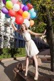 Señora hermosa en el equipo retro que sostiene un manojo de globos en el ci Imágenes de archivo libres de regalías