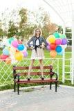 Señora hermosa en el equipo retro que sostiene un manojo de globos en el ci Imagen de archivo libre de regalías