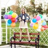 Señora hermosa en el equipo retro que sostiene un manojo de globos en el ci Imagenes de archivo