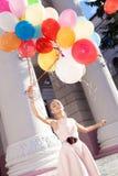 Señora hermosa en el equipo retro que sostiene un manojo de globos en el th Fotos de archivo libres de regalías
