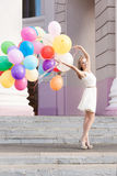 Señora hermosa en el equipo retro que sostiene un manojo de globos en el th Imagen de archivo libre de regalías