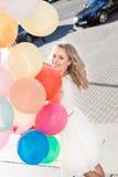 Señora hermosa en el equipo retro que sostiene un manojo de globos en el th Foto de archivo libre de regalías