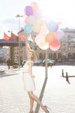 Señora hermosa en el equipo retro que sostiene un manojo de globos en el th Foto de archivo