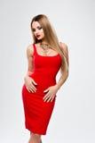 Señora hermosa en vestido rojo con los labios rojos del maquillaje brillante, mujer joven magnífica del busto A con el pelo largo Fotografía de archivo
