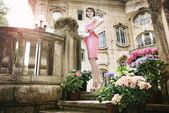 Señora hermosa en vestido rosado, delante de un b viejo Imagenes de archivo