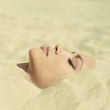 Señora hermosa enterrada en la arena Foto de archivo libre de regalías
