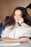 Señora hermosa joven que miente en el sofá con el libro abierto Foto de archivo
