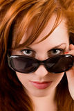 Señora hermosa Looking Over Sunglasses del Redhead Imagenes de archivo