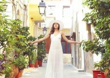 Señora hermosa que camina abajo de la calle en un vestido blanco Foto de archivo libre de regalías
