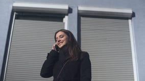 Señora hermosa que comprueba el app móvil en el teléfono, colocándose al aire libre, llamando el taxi almacen de video