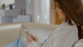 Señora hermosa que mecanografía, enviando el mensaje, mandando un SMS de smartphone metrajes