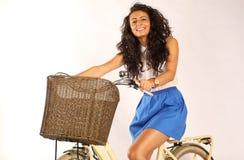 Señora hermosa que monta su bici en el estudio Imagenes de archivo