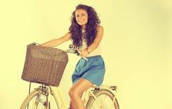 Señora hermosa que monta su bici en el estudio Fotos de archivo libres de regalías