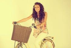 Señora hermosa que monta su bici en el estudio Imágenes de archivo libres de regalías