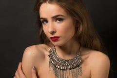Señora hermosa que presenta con el collar en estudio Fotografía de archivo